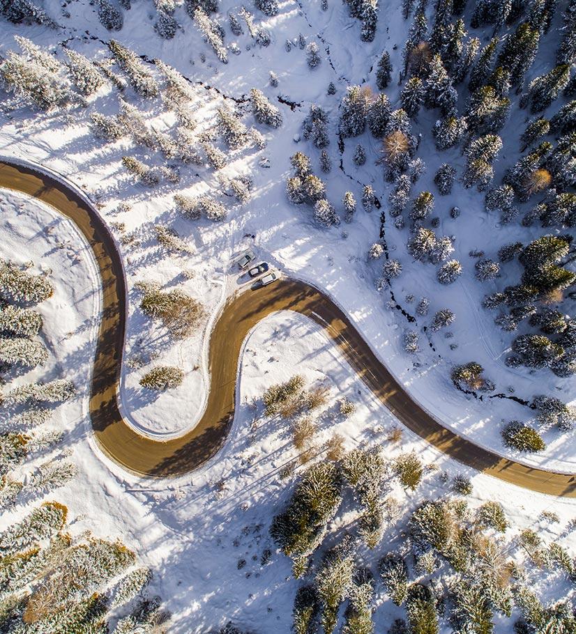 Kurvenreiche Strasse aus der Vogelperspektive, Landschaft bedeckt mit Schnee